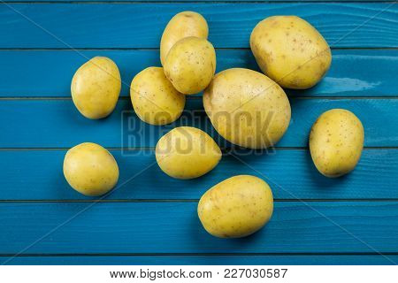 Border Of Assorted Fresh Healthy Potatoes On A Rustic Blue Wood Background With Central Copy Space I