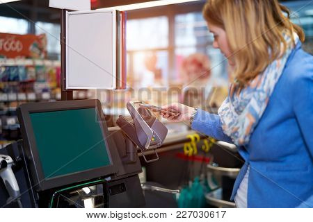 Young Woman Making Self-checkout In Supermarket With Mobile Phone