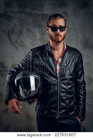 Portrait Of Redhead Male In Motorcycle Leather Jacket Hold Safety Helmet On Grey Background.