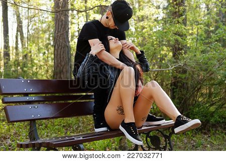 Sexy Female With Tattooes On Legs Posing With Her Boyfriend In Summer Park.