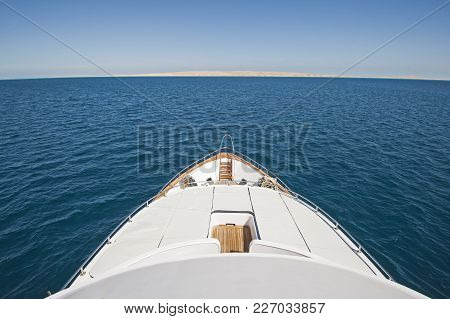 View over the bow of a large luxury motor yacht on tropical open ocean with sun beds