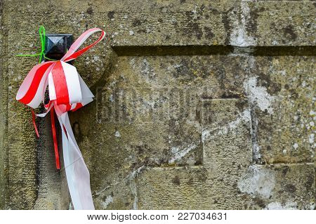 Ribbon With National Colours Of Poland Tied Up To The Old Gravestone On The Cemetery. All Saints Day