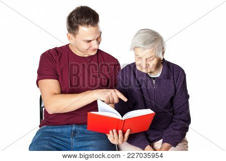 Handsome Young Man Reading A Novel With Elderly Disabled Grandmother On Isolated Background