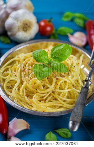 Metal Plate Of Cooked Italian Spaghetti Pasta Surrounded By Fresh Ingredients Including Garlic Clove