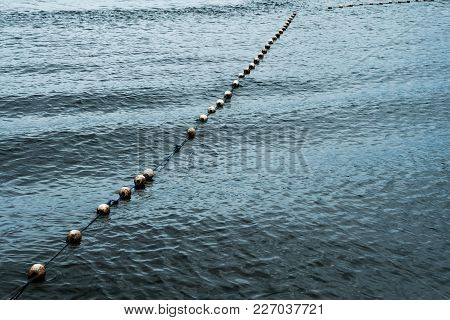 Line Of White Saferty Buoy On Seascape. Concept Of Lifeguard Details In Ocean
