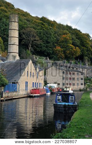 Scenic View Of Hebden Bridge With Historic Buildings Along The Canal And Moored Houseboats With Towp