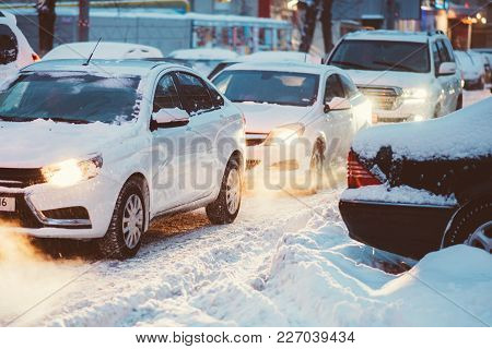 Cars Go On A Snowy Road In The Evening