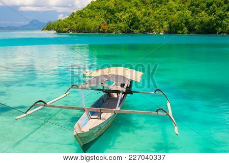 Traditional Boat Floating On The Transparent Blue Toned Lagoon Of The Remote Togean (or Togian) Isla