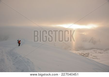 Snowboarder Walking On The High Mountain Peak Covered With Snow Under The Golden Sun Rays