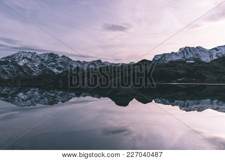 High Altitude Alpine Lake In Idyllic Landscape. Reflection Of Snowcapped Mountain Range And Scenic C