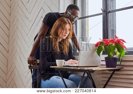African American Male And Caucasian Female Working With A Laptop At The Table.