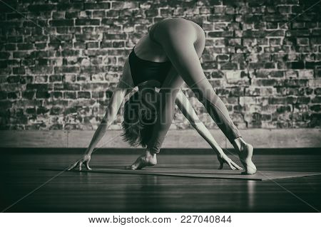 Beautiful Young Woman Practices Yoga Asana At The Yoga Studio On A Brick Wall Background.