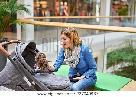 Young Smiling Woman Sitting On Bench With Stoller In Shopping Center And Showing Soft Toy To Her Bab