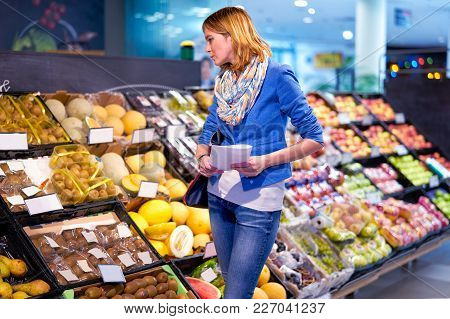 Young Stylish Woman In Blue Jacket Staying Confused With Shopping List In Grocery Store