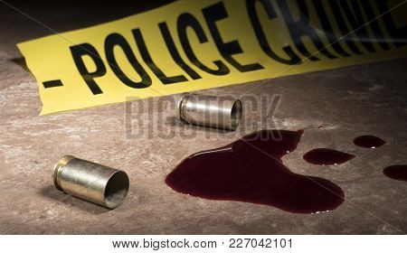 Police Line Tape And Two Semi Auto Pistol Cartridges Next To Blood On The Floor