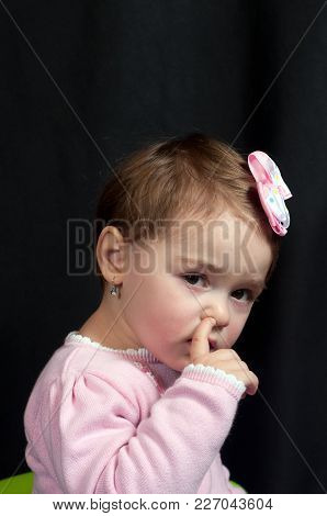 A Young Girl Caught In The Act Of Picking Her Nose.