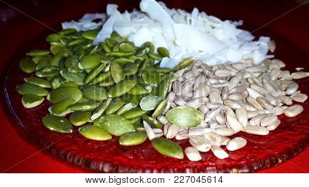 Healthy Snacks. Pumpkin Seeds, Sunflower And Coconut Flakes On A Plate, On A Red Tablecloth.