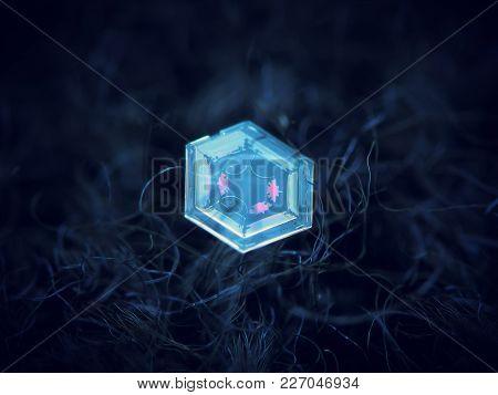 Real Snowflake Glittering On Dark Blue Background. Macro Photo Of Real Snow Crystal: Simple Hexagona