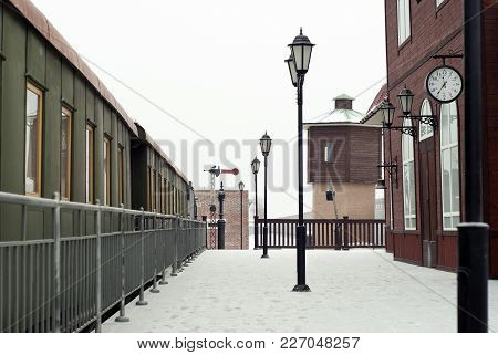 Fragment Of A Vintage Railway Station With Old Wagons Standing In Rails In A Winter Landscape