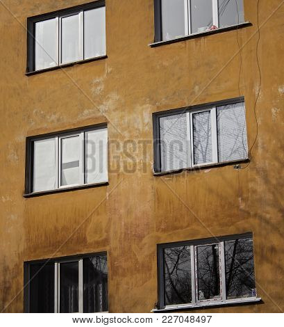 Yellow wall of the old house. Old architecture. Old house. Yellow wall. Windows. Grunge house.