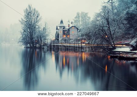 Bled, Slovenia. Foggy Morning In Bled Lake With A Boat And House In Slovenia. Fog Over The Forest. F