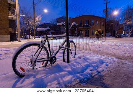 Montreal, Ca - 17 February 2018: Bike Covered In Snow During Snow Storm As Someone Is Riding A Bike