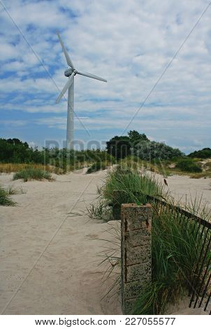 Bright Picture Of Abandoned Wind Turbine Standing On A Seaside Surrounded By Bushes And Sand. A Piec