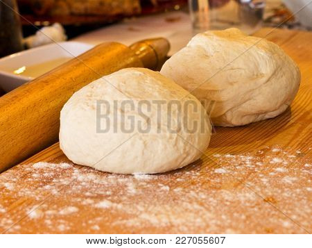 Yeast Dough In Flour On A Wooden Board With Rolling Pin