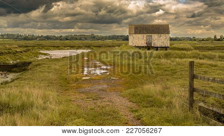 House On Stilts In The Marshland Near The River Crouch, Wallasea Island, Essex, England, Uk