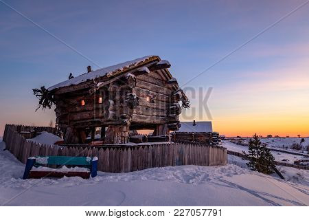 Traditional Log House. The Facade Of The Building Against The Evening Sky In Winter. Wooden Fence An