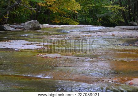 A Mountain Stream Flowing Over Smooth Rock