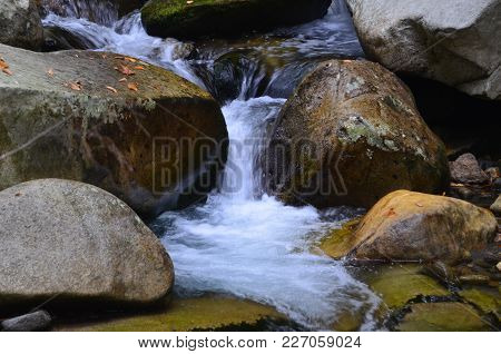 A Waterfall Flowing Through Some Big Rocks