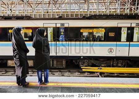 Tehran, Iran - April 29, 2017: Two Young Muslim Women, Dressed In Black Chador, Are Waiting For The