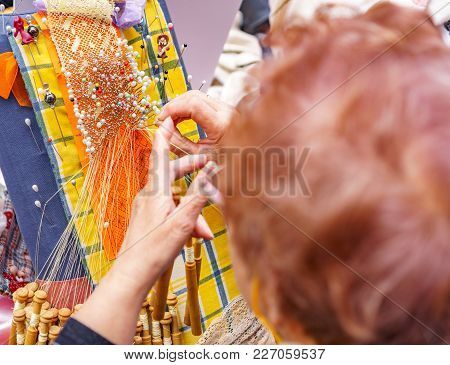 Detailed View Of An Elderly Woman Head And Hands Working With Bobbin Lace