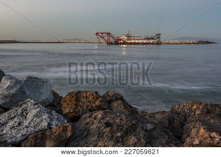 Dredge Working Into The Dawn Hours In The Pacific Ocean Clearing The Harbor Mouth.