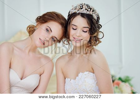Two Girls In Wedding Dresses. Beautiful Delicate Girls In The Bridal Salon. Close-up