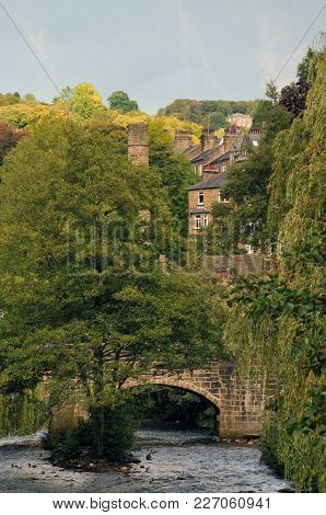 Hebden Bridge Town In Summer With Packhorse Bridge In Summer Tree Lined River And Buildings And Old