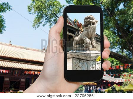 Travel Concept - Tourist Photographs Outdoor Lion Statue In Guangxiao Buddhist Temple (bright Obedie