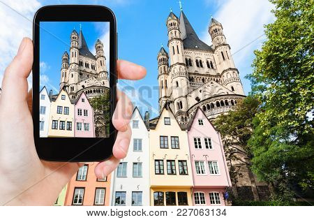Travel Concept - Tourist Photographs Old Houses On Fischmarkt Square And Great St Martin Church In C