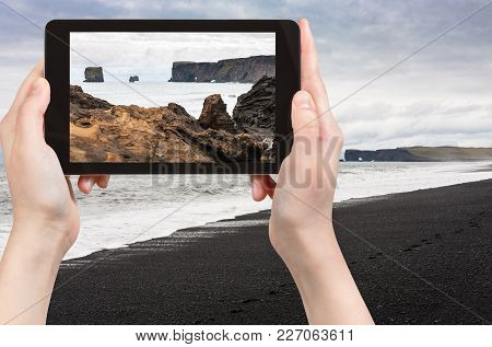 Travel Concept - Tourist Photographs Atlantic Ocean Volcanic Coast And View Of Dyrholaey Promontory