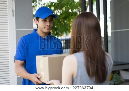 Handsome Young  Man Delivery Person In Blue Uniform Holding Cardboard Box Send To Customer,delivery