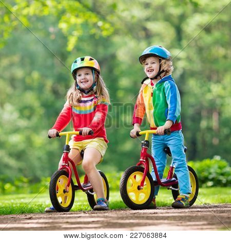Children Riding Balance Bike. Kids On Bicycle In Sunny Park. Little Girl And Boy Ride Glider Bike On