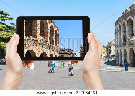Travel Concept - Tourist Photographs Roman Arena On Piazza Bra In Verona In Spring In Italy On Table