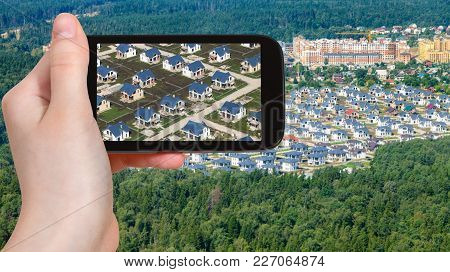 Travel Concept - Tourist Photographs New Cottages With Lawn In Moscow Region In Russia On Smartphone