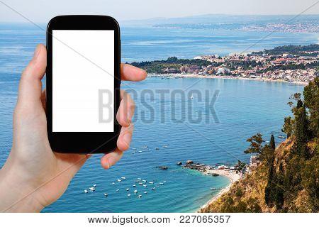 Travel Concept - Tourist Photographs Ionian Sea Coastline With Giardini Naxos Town In Sicily Italy I