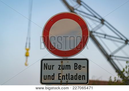 Symbol: No Vehicles, Text: Only For Loading And Unloading (german), With A Blurry Crane In The Backg