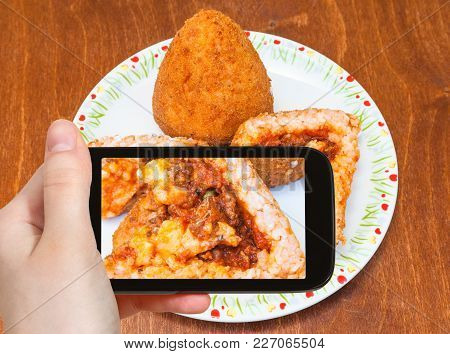 Travel Concept - Tourist Photographs Meat Ragu Stuffed Rice Balls Arancini On Plate (traditional Sic
