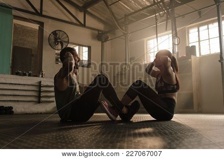 Young Couple Resting After Work Out At Gym. Fitness People Sitting And Relaxing In At Health Club Af