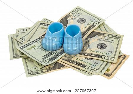 Horizontal Shot Of A Pair Of Blue Plastic Baby Booties Resting On A Pile Of Twenty Dollary Bills.