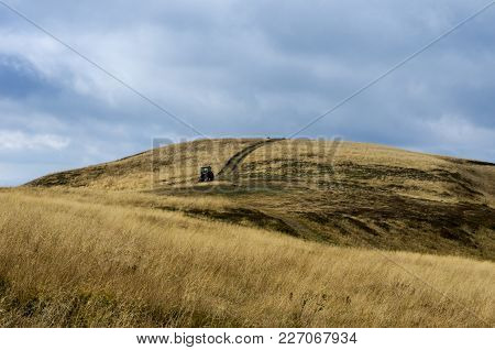 Tractor In The Mountains. The Road Leading To The Top Of The Mountain. Yellow Autumn Grass.
